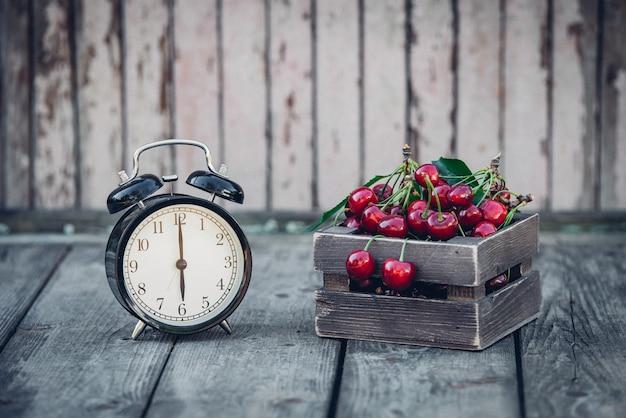 Zomertijd, rode kers en een wekker op een oude houten tafel