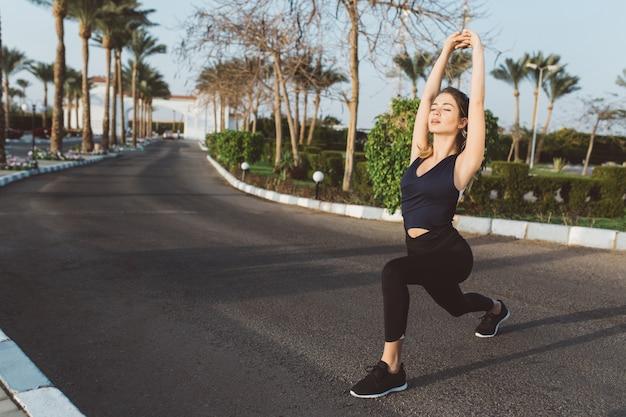 Zomertijd van vrolijke jonge vrouw die zich uitstrekt op straat in tropische stad. yoga doen, opgewekte stemming, zonnige ochtend, training, aantrekkelijk model, ontspannen.