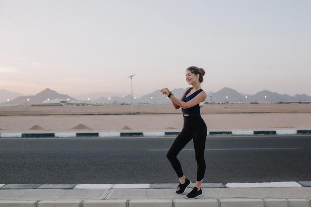 Zomertijd van vrolijke jonge vrouw in sportkleding wandelen, horloge aan kant kijken, glimlachend op weg in tropisch land. vrolijke stemming, training, zonnige ochtend, aantrekkelijk model.