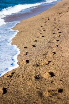 Zomervakantie achtergrond - voetafdrukken op het strand met gouden zand