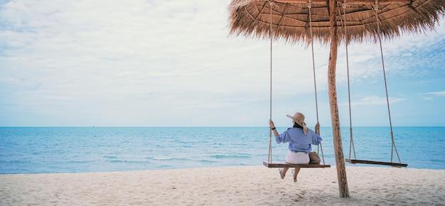 Zomervakantie concept jonge vrouw, gekleed in stijlvolle blauwe jurk en strooien hoed met blauwe lucht op het strand.