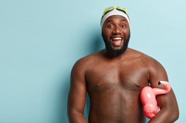 Zomervakantie concept. vrolijke atletische man heeft een donkere huid, lacht en toont witte tanden