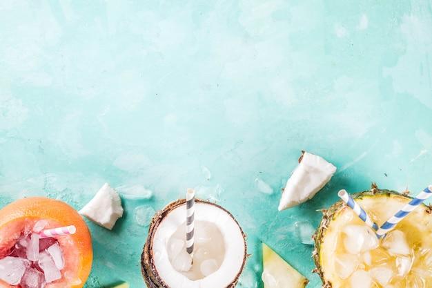Zomervakantie drankje concept, stel verschillende tropische cocktails of sappen in ananas, grapefruit en kokosnoot met ijs, lichtblauw beton