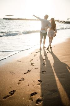 Zomervakantie en reizen. sexy vrouw en man in zeewater bij zonsondergang. verliefde paar ontspannen op het strand van zonsopgang. liefdesrelatie van een stel dat samen geniet van een zomerdag. selectieve focus
