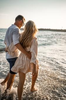 Zomervakantie en reizen. sexy vrouw en man in zeewater bij zonsondergang. verliefde paar ontspannen op het strand van zonsopgang. liefdesrelatie van een stel dat samen geniet van een zomerse dag