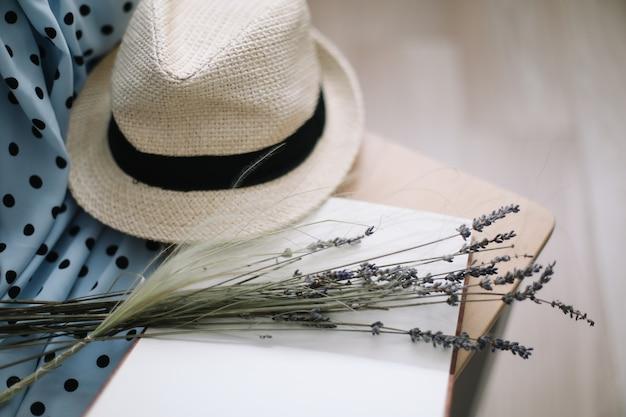 Zomervakantie en vakanties achtergrond met een blauwe jurk strohoed bloemen en een boek