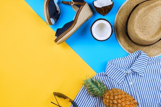 Zomervakantie flatlay met strohoed, espadrilles, kokosnoothelften, lichaamsolie, gestripte jurk en bril op blauw en geel met copyspace