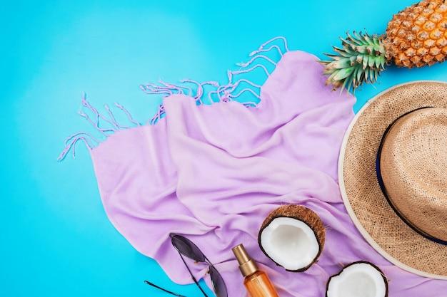 Zomervakantie flatlay met strohoed, roze sjaal, ananas, kokosnoot, lichaamsolie en glazen op blauw met copyspace