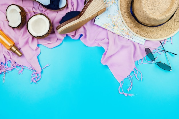 Zomervakantie flatlay met strohoed, roze sjaal, espadrilles, kokosnoot, lichaamsolie en glazen op blauw met copyspace