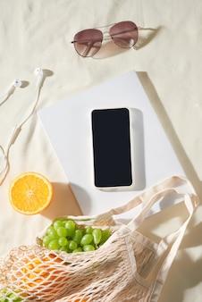Zomervakantie, gadget, fruit, camera, sap op lichte stof achtergrond. picknick concept.