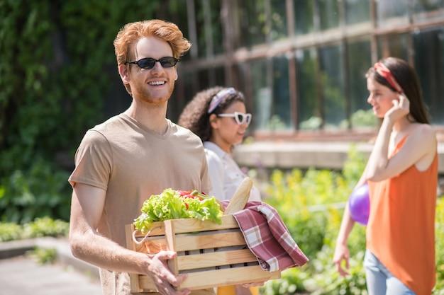Zomervakantie. gelukkige kerel in zonnebril met doos picknickvoedsel en twee kletsende vriendinnen achter in het park op warme dag