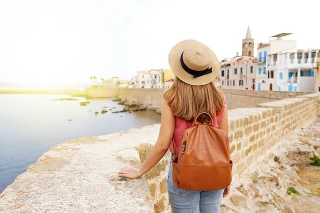 Zomervakantie in italië. achteraanzicht van jonge vrouw met hoed en rugzak in alghero, oude stad, sardinië, italië.