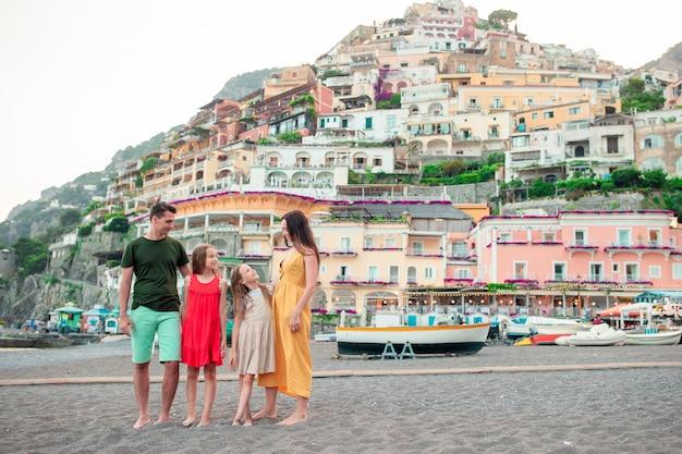 Zomervakantie in italië. familie in positano-dorp op de achtergrond, amalfi kust, italië
