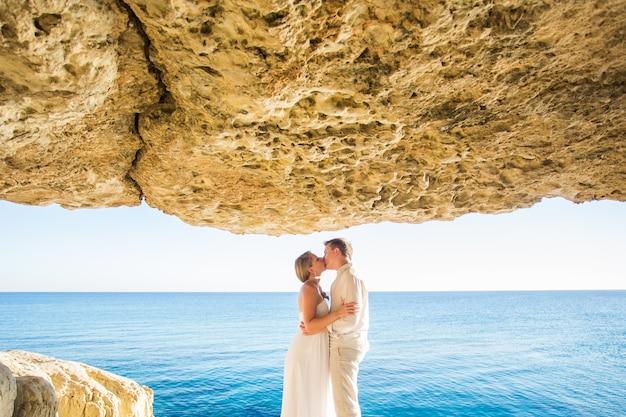 Zomervakantie, mensen, liefde en daterend concept - gelukkig paar die en bij de zomer overzeese achtergrond koesteren kussen