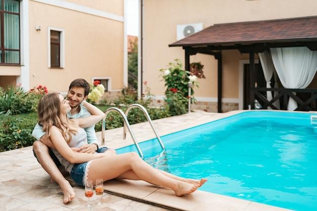 Zomervakantie, mensen, romantiek, dating concept, koppel mousserende wijn drinken terwijl u geniet van tijd samen bij het zwembad