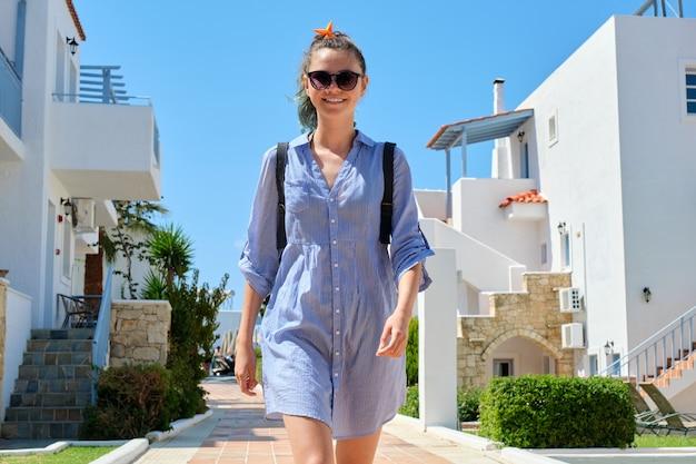 Zomervakantie, mooie tiener meisje wandelen in resort sea spa hotel. aangelegd, hotel huizen achtergrond. vrije tijd, recreatie, toerisme, levensstijl van jongeren, adolescenten