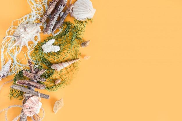 Zomervakantie ontspanning thema met schelpen, hoed, zonnebril en camera op geel