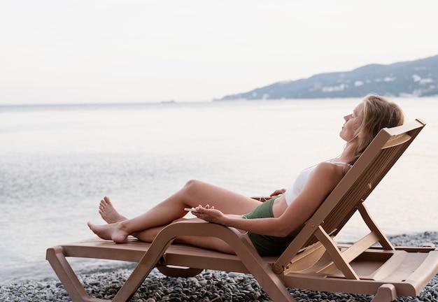 Zomervakantie op het strand. de mooie jonge vrouw in zwembroek die op de ligstoel ligt en naar de muziek luistert met behulp van een mobiel apparaat, blauw uur