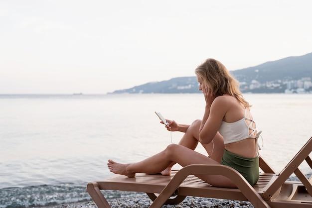 Zomervakantie op het strand. de mooie jonge vrouw in zwembroek zittend op de ligstoel luisteren naar de muziek met behulp van mobiel apparaat, blauwe uur