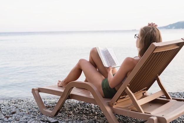 Zomervakantie op het strand. de mooie jonge vrouw in zwempak zittend op de ligstoel die een boek leest en ontspant, blauw uur