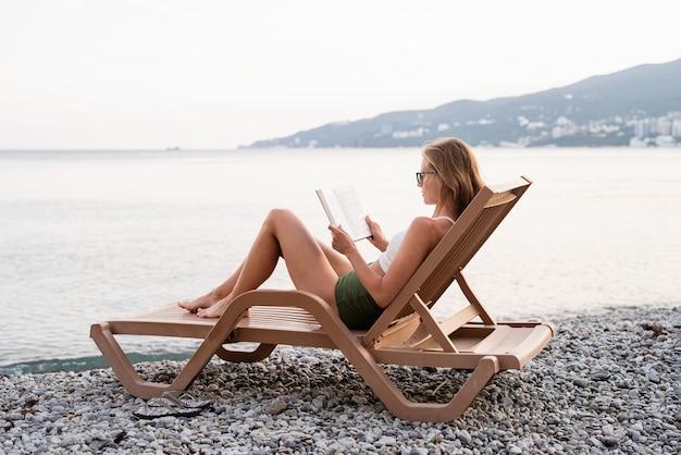 Zomervakantie op het strand. de mooie jonge vrouw in zwempak zittend op de ligstoel een boek lezen en ontspannen