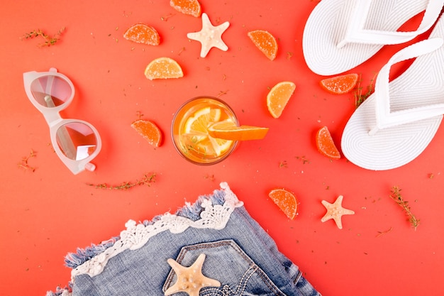 Zomervakantie oranje fruitcocktail detox water in de buurt van witte slippers, korte broeken en zonnebrillen