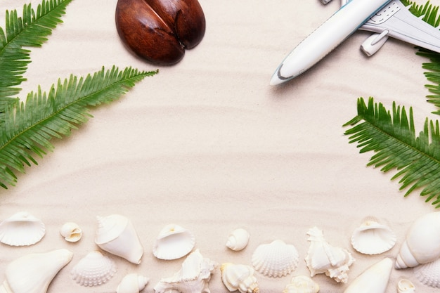 Zomervakantie plat lag op tropisch zandstrand oceaan strand. vakantieconcept met vliegtuig, schelpen, palmbladeren - zomerse levensstijl, bovenaanzicht arrangement