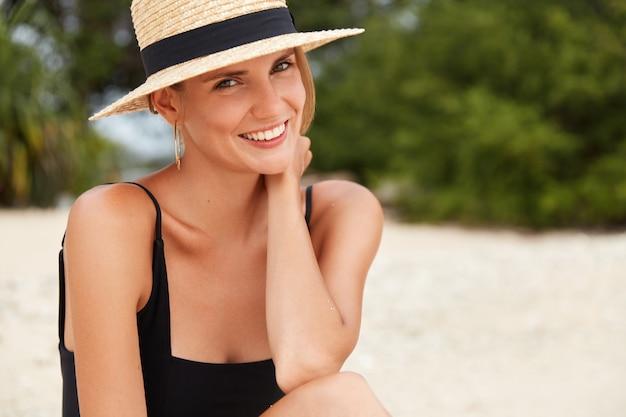 Zomervakantie, reizen en vakantie concept. bijgesneden schot van prachtige opgetogen vrouw draagt zwarte zwembroek en strooien hoed, vormt tegen de groene vegetatie op tropisch strand, bewondert zonneschijn.