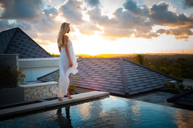 Zomervakantie reizen strand foto jonge mooie blonde meisje in witte jurk in pool
