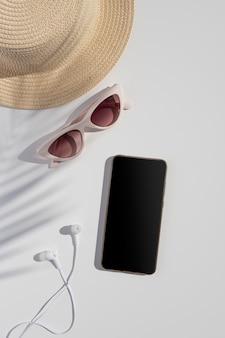 Zomervakantie telefoonmodel. reis verticaal plat met een telefoon met een leeg scherm, palmbladschaduw, oortelefoons en strohoed. kopieer ruimte voor een mobiele app of screenshot van de site