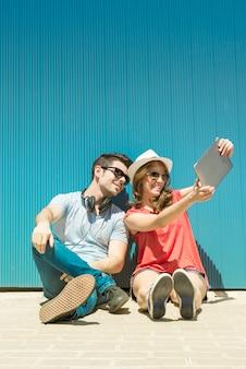 Zomervakantie, tiener- en technologieconcept - paar lachende tieners in zonnebril die selfie maken met tablet pc