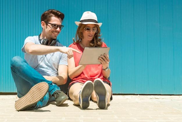 Zomervakantie, tiener- en technologieconcept - tieners kijken naar tablet-pc