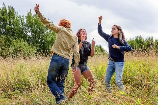 Zomervakantie vakantie gelukkige mensen concept. groep van drie vrienden jongen en twee meisjes dansen en plezier samen buitenshuis. picknick met vrienden op road trip in de natuur.