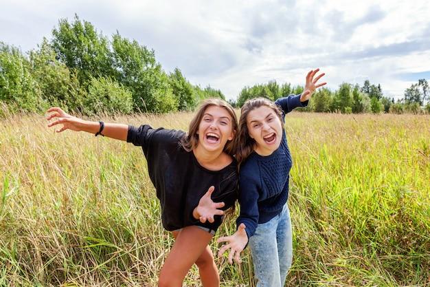 Zomervakantie vakantie gelukkige mensen concept. groep van twee vriendinnen dansen knuffelen en plezier samen in de natuur buitenshuis. mooie momenten beste vriend.