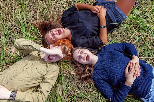 Zomervakantie vakantie gelukkige mensen concept. hoogste meningsgroep van drie vrienden die op gras in cirkel liggen die en pret samen in openlucht glimlachen hebben. picknick met vrienden op road trip in de natuur.