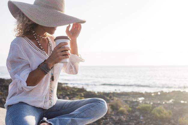 Zomervakantie, vakantie, reizen en mensen concept - lachende vrouw in zonnehoed en glas koffie of drankje op het strand over zee en blauwe lucht