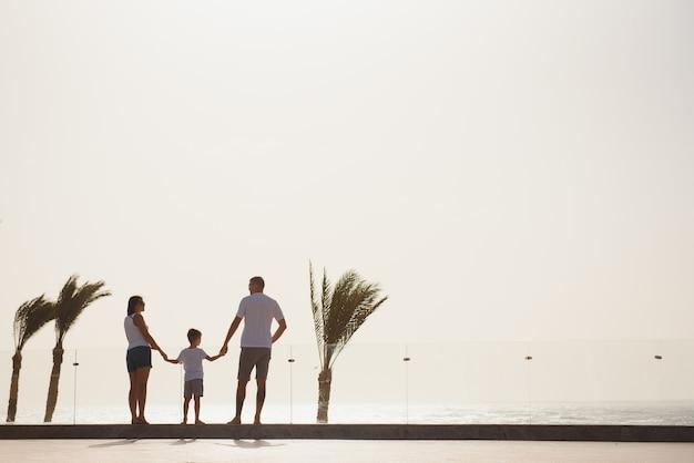 Zomervakantie van gelukkige familie. moeder en vader met zoon lopen op strandpalmen. kind met vader en moeder. familie reizen met kind op moeder- of vaderdag. liefde en vertrouwen als familiewaarden.