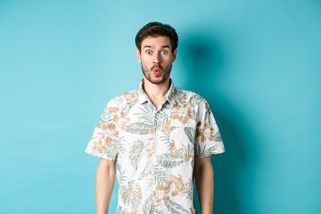 Zomervakantie. verraste toerist zegt wow en starend naar de camera, terwijl hij geweldige promo bekijkt, staande in een hawaiiaans shirt op een blauwe achtergrond.