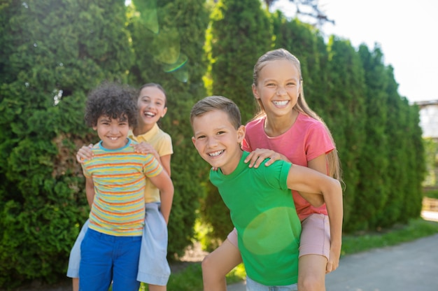 Zomervakantie. vrolijke gastvrije vrienden van basisschoolleeftijd die actief zomervakanties doorbrengen in groen park