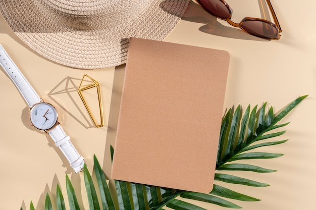 Zomervakantie werk en plat leggen. palmbladeren, strooien hoed, zonnebril en notitieboekje met blanco kraftpapier omslag. ruimte voor kladblokprint