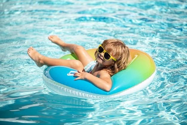 Zomervakantie zomer kinderweekend jongen in zwembad grappige jongen op opblaasbare rubberen cirkel