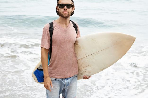 Zomervakanties, actieve levensstijl en vrije tijd concept. openluchtportret van jonge surfer in zwarte schaduwen die witte surfplank onder zijn wapen en het kijken houden
