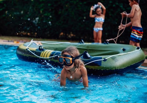 Zomervakanties in thailand. drie vrolijke en speelse kinderen genieten van hun reis zwemmen in zwembad met boot.