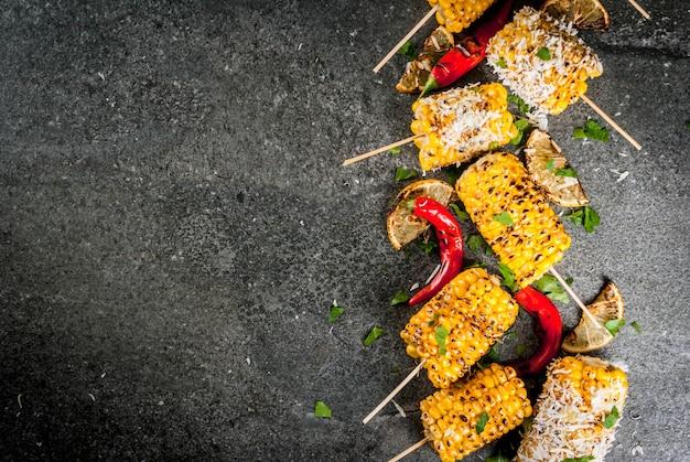 Zomervoedsel ideeën voor barbecue- en grillpartijen gegrilde maïs gegrild in vuur met een sprenkel van kaas (mexicaanse elotes) hete chili peper en citroen