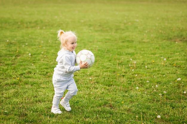 Zomerwandeling, meisje op de natuur. sport familie. een klein meisje voetballen met een bal.