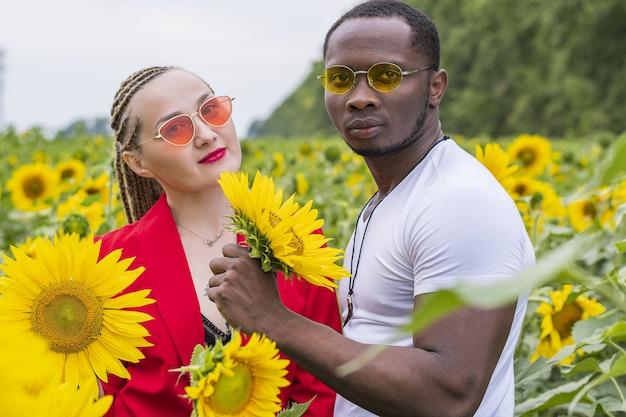 Zomerwandeling van een verliefd stel in zonnebloemen bij zonsondergang