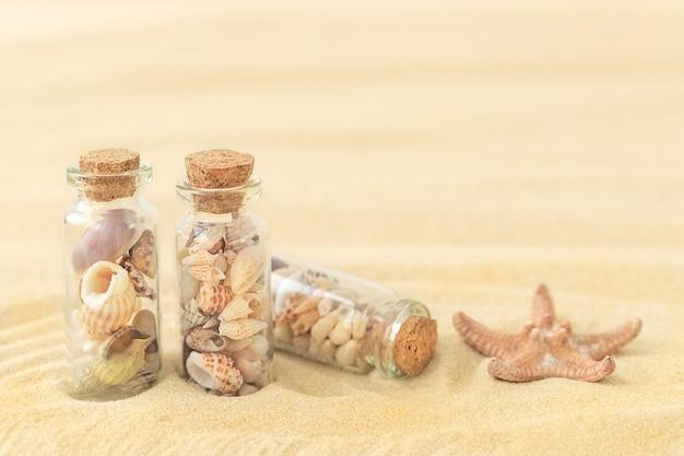 Zomerzandige ondergrond met schelpen in kleine glazen flesjes en zeesterren