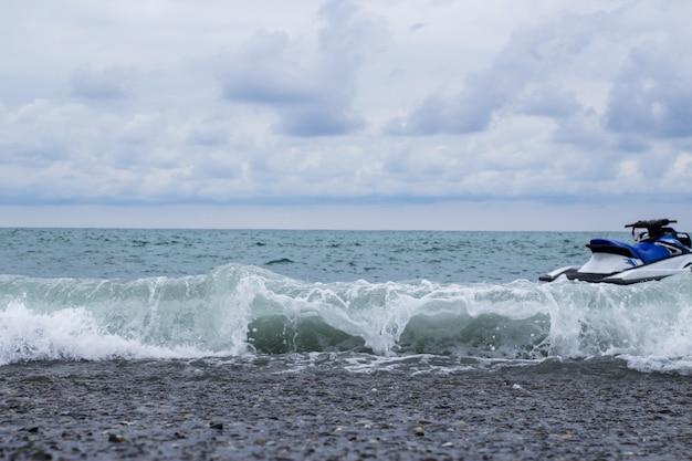 Zomerzeegezicht vanaf de kust, de golf rolt aan wal op de kiezels van de zee