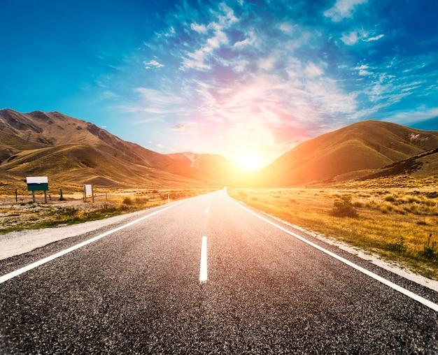 Zon aan de horizon van de weg