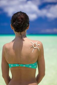 Zon gemaakt met zonnebrandcrème op de schouder van de vrouw
